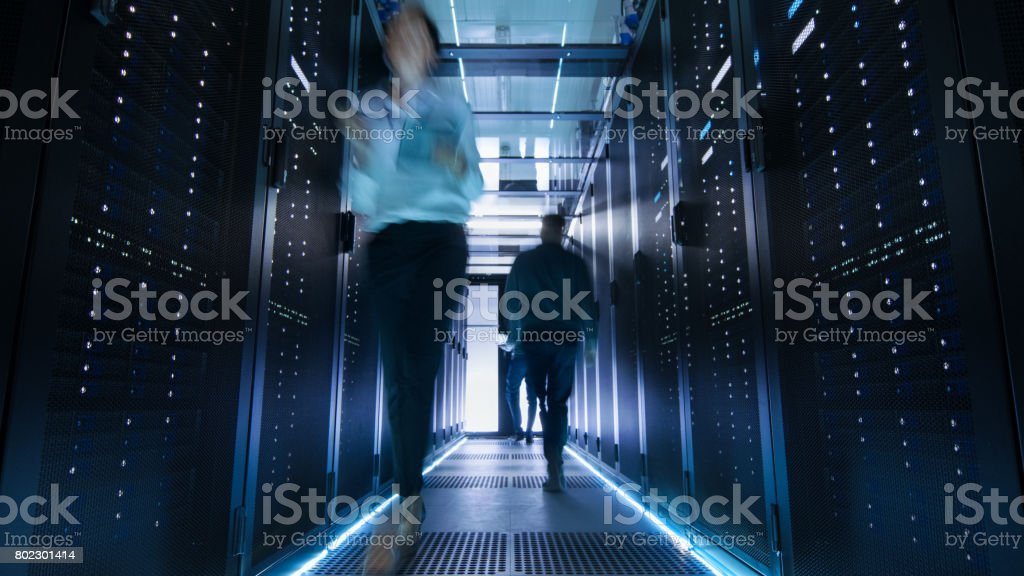 Shot of Corridor in Large Data Center Full of Walking and Working People. Pronounced Motion Blur. stock photo