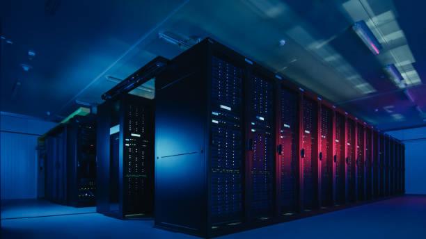 shot van data center met meerdere rijen van volledig operationele server racks. moderne telecommunicatie, cloud computing, kunstmatige intelligentie, database, supercomputer technologie concept. geschoten in het donker met neon blauw, roze lichten. - datacenter stockfoto's en -beelden