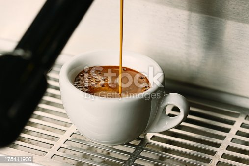 Close up action photo of a shot espresso extraction into a demitasse cup.