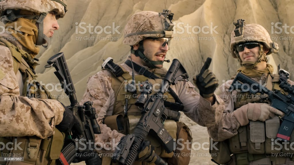 Shot of Fully Equipped Group of Soldiers Planning Their Actions Before Military Operation in the Desert. stock photo