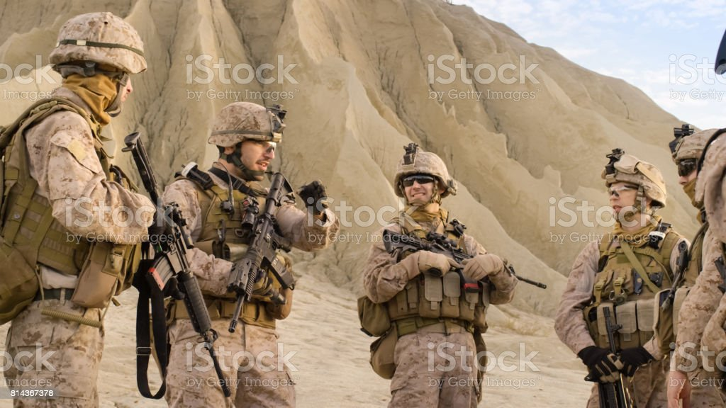 Shot of Fully Equipped Group of Soldiers Standing in a Circle and Planning Their Actions Before Military Operation in the Desert. stock photo
