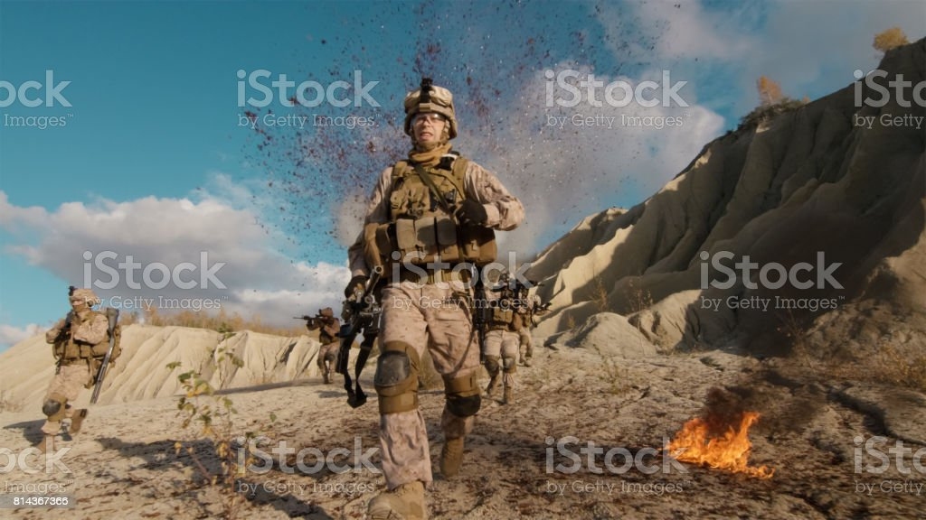 Shot of Fully Equipped Soldier Running Away From the Explosion. His Squad is Being Attacked and Bombed During Combat in the Desert. stock photo