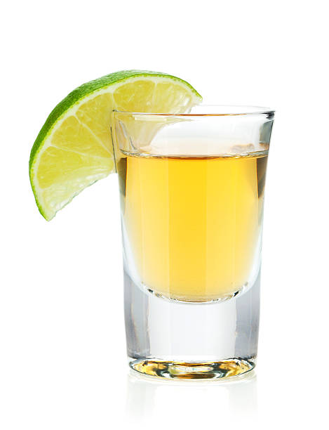 Shot of gold tequila with lime slice Shot of gold tequila with lime slice. Isolated on white background tequila shot stock pictures, royalty-free photos & images