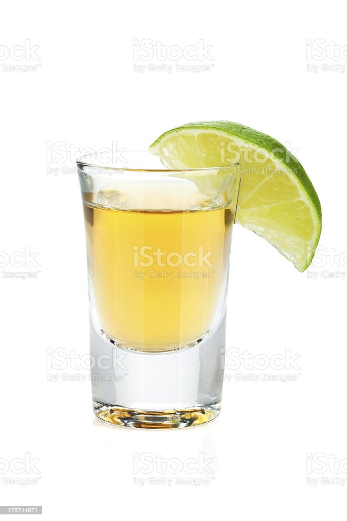 Shot of gold tequila with lime slice stock photo
