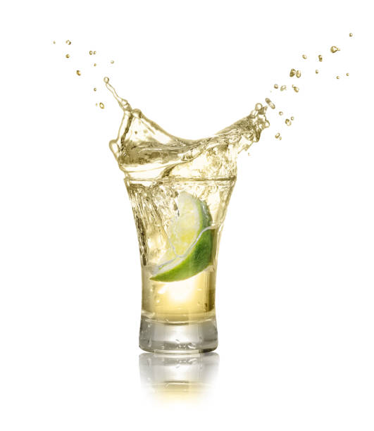 shot of gold tequila with splash gold tequila shot with lime slice and splash isolated on white background. Lime is falling in the alcohol drink. Splash of tequila from the falling piece of lime tequila shot stock pictures, royalty-free photos & images