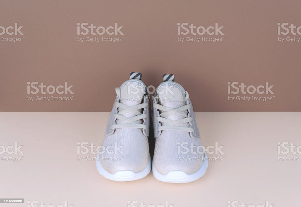 Shot of golden sneakers on beige background royalty-free stock photo
