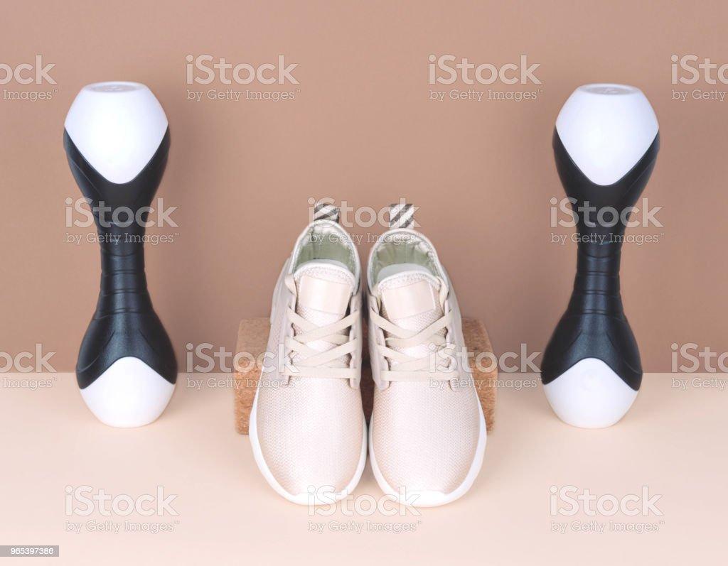 Shot of golden sneakers on beige background zbiór zdjęć royalty-free