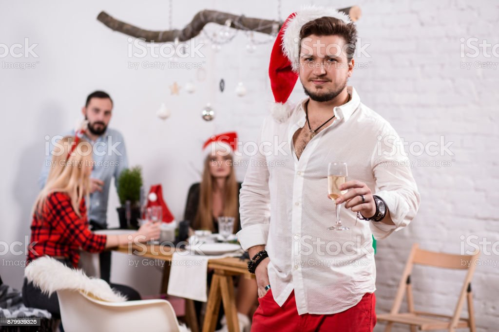 Shot of happy friends enjoying holidays. Focus on the man in the foreground in a red Christmas hat stock photo