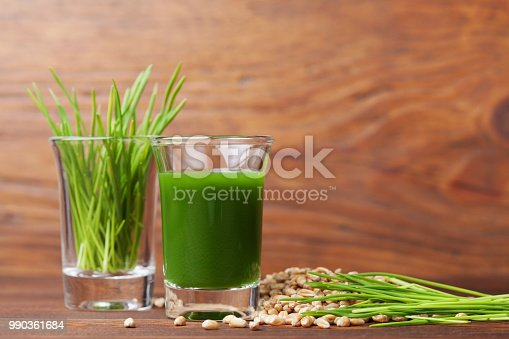 Shot of healthy wheat grass juice. Fitness, diet and detox beverage. Superfood. Copy space for text.