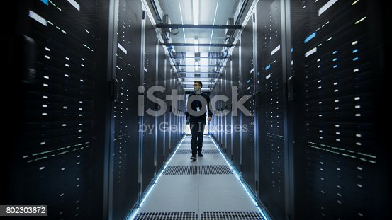 899720520istockphoto Shot of IT Engineer Walking Through Data Center Corridor with Rows of Rack Servers. 802303672
