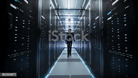 802317162istockphoto Shot of IT Engineer Walking Through Data Center Corridor with Rows of Rack Servers. 802303672