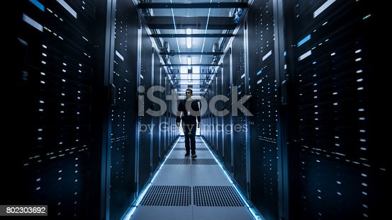 802303638istockphoto Shot of IT Engineer Walking Through Data Center Corridor with Rows of Rack Servers. 802303692