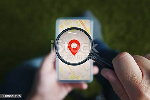 Shot of male hands holding magnifying glass with the red icon of geo-location and looking through it to the smartphone with online city map on the screen. Concept of using mobile net for navigation