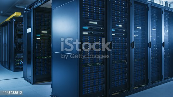 Shot of Modern Data Center With Multiple Rows of Operational Server Racks. Modern High-Tech Database Super Computer Clean Room.