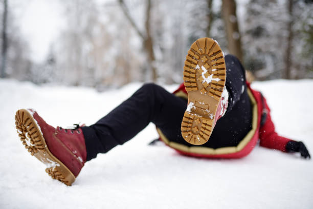 Shot of person during falling in snowy winter park. Woman slip on the icy path, fell and lies. Shot of person during falling in snowy winter park. Woman slip on the icy path, fell and lies. Danger of season trauma. slippery stock pictures, royalty-free photos & images