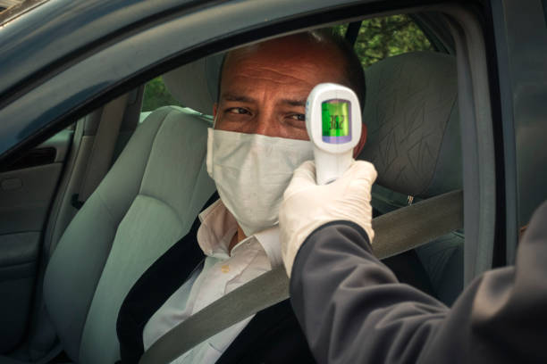 Shot of policeman measuring a healthy senior adult's body temperature in his car stock photo