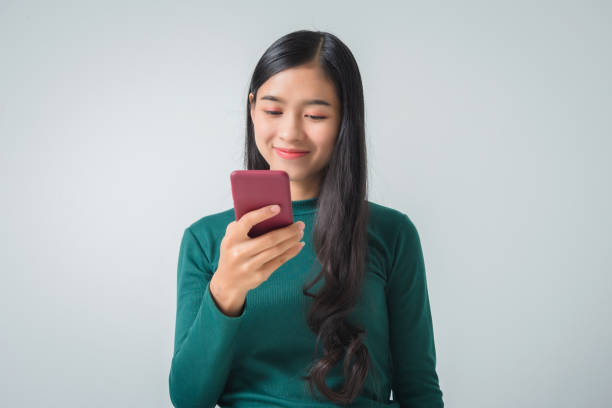 Shot of pretty young female holds modern smart phone amazed by unbelievable message winner, happy feeling. stock photo
