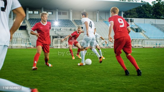 istock Shot of Professional Soccer Player Leads with a Ball, Masterfully Dribbling and Bypassing Sliding Tackles of His Opponents. Two Professional Teams are Playing Football Championship. 1161534927