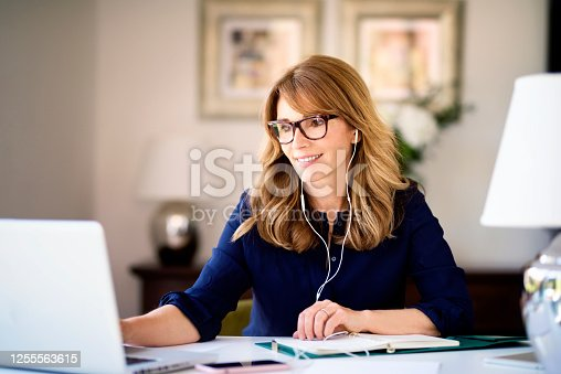 Shot middle aged woman sitting at desk behind her laptop and having video conference while working from home. Home office.