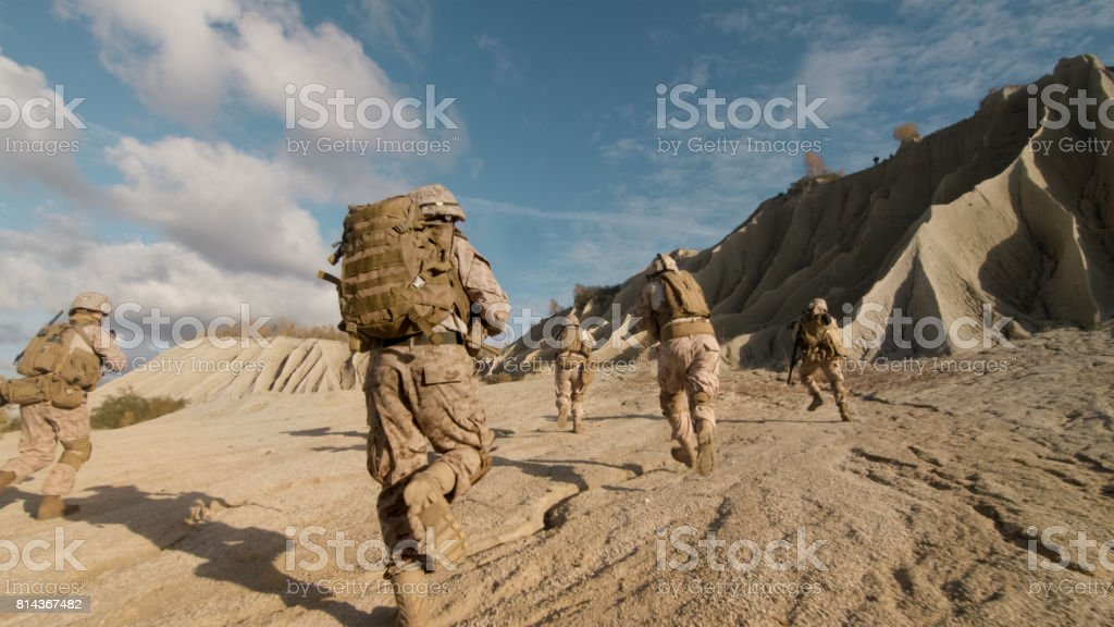 Shot of Squad of Soldiers Running Forward and Atacking Enemy During Military Operation in the Desert. stock photo