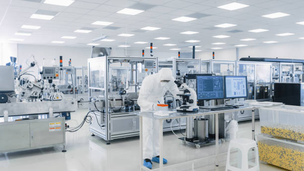 Shot of Sterile Pharmaceutical Manufacturing Laboratory where Scientists in Protective Coverall's Do Research, Quality Control and Work on the Discovery of new Medicine. Shot of Sterile Pharmaceutical Manufacturing Laboratory where Scientists in Protective Coverall's Do Research, Quality Control and Work on the Discovery of new Medicine. computer chip stock pictures, royalty-free photos & images
