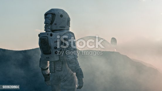 istock Shot of the Astronaut on Red Planet Watching Toward His Base/Research Station. Near Future First Manned Mission To Mars, Technological Advance Brings Space Exploration, Colonization. 935639864