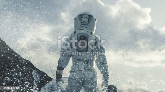 istock Shot of the Astronaut Walking Through Blizzard on Frozen Alien Planet Towards His Base/ Research Station. Technological Advance Brings Space Exploration, Colonization. 935639718