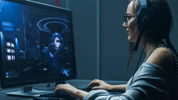 shot of the beautiful professional gamer girl playing in first-person shooter online video game on her personal computer. casual cute geek wearing glasses and talking into headset. in the basement gaming club. - esports stock photos and pictures