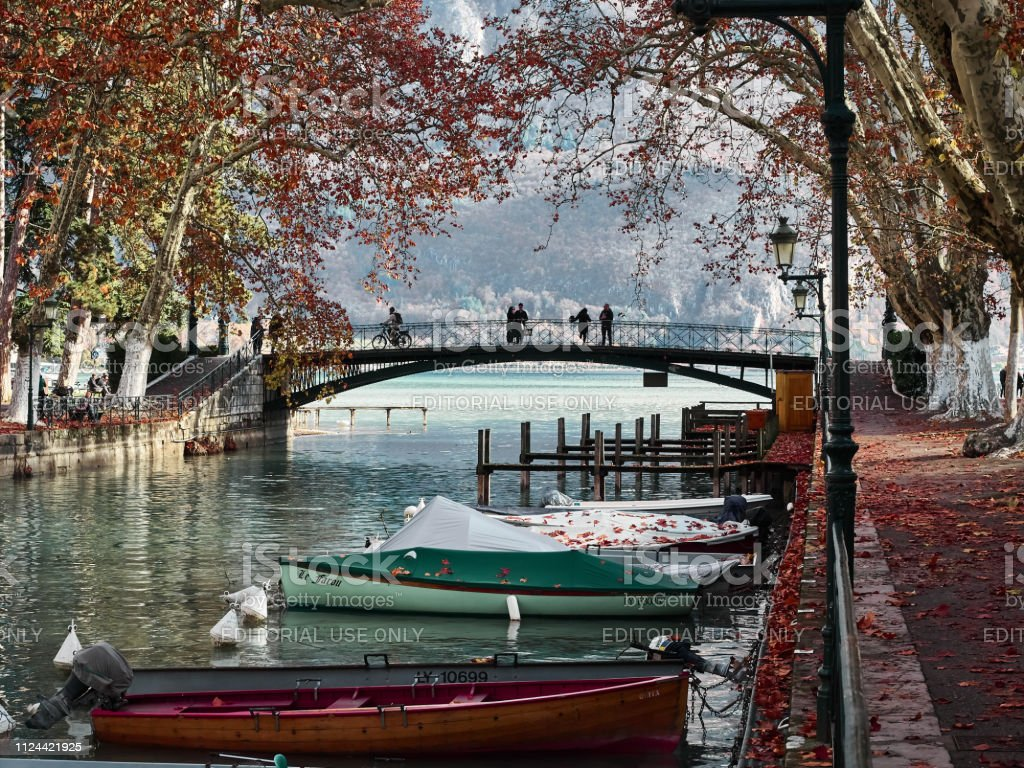 Shot of the Canal du Vassè which brings to the Pont Des Amours Annecy, France - December 07, 2018 - Shot of the Canal du Vassè, the canal full of boats which brings to the famous Pont Des Amours in Annecy, France. The shot is taken during a sunny day. People are visiting the bridge. Annecy Stock Photo