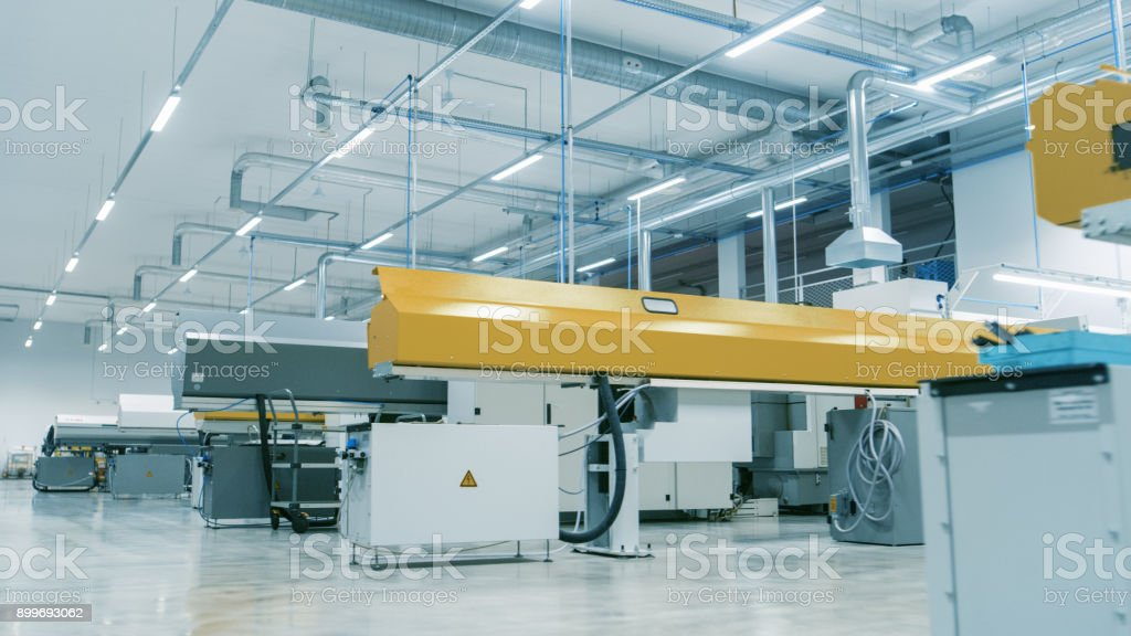 Shot of the High-Tech Modern Electronics Manufacturing Factory Full of Computerized Automatic Machinery. Facility is Bright and Clean. stock photo