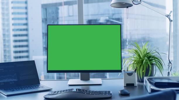 shot van de bureau met groene mock-up scherm personal computer permanent op het. moderne stijlvolle kamer met uitzicht op een grote zakenwijk van de stad. - green screen stockfoto's en -beelden
