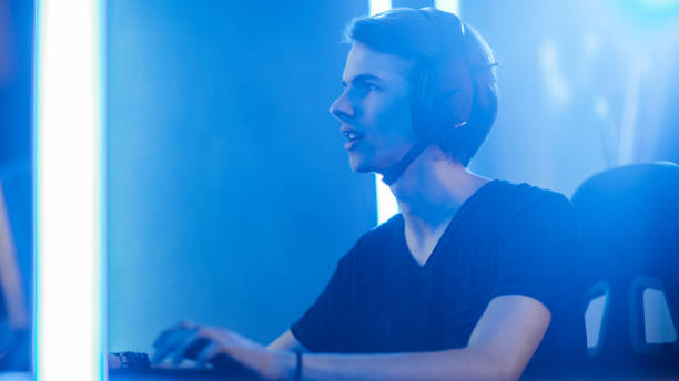Shot of the Pro Gamer Playing in Video Games on His Personal Computer. Talking with His Team through Microphone on Headphones. Retro Neon Room. stock photo