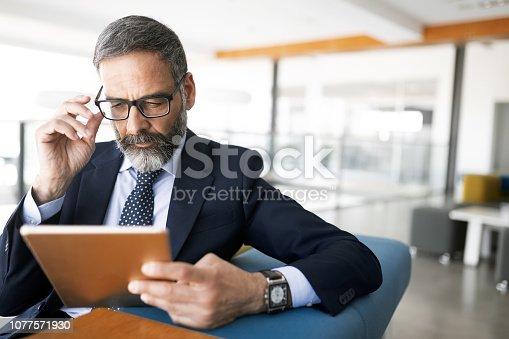 istock Shot of thinking financial advisor businessman working in office. 1077571930