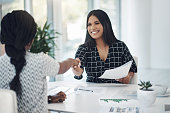 istock Shot of two young businesswomen shaking hands in a modern office 1315012808