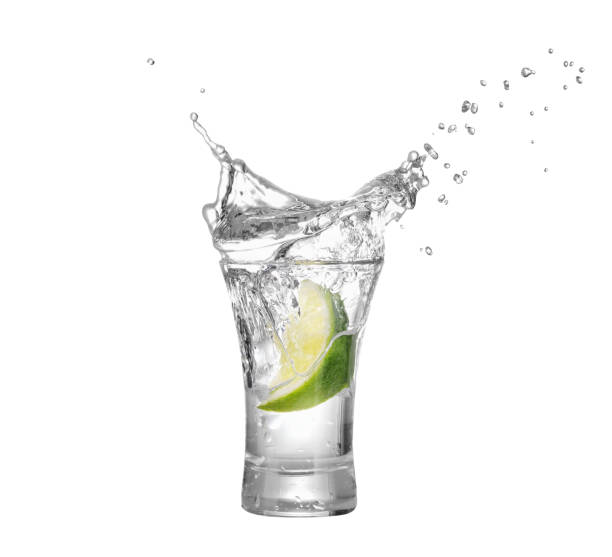 shot of vodka or tequila with lime slice shot of vodka or tequila with lime slice and splash isolated on white background. Lime is falling in the alcohol drink. Splash of vodka  from the falling piece of lime tequila shot stock pictures, royalty-free photos & images