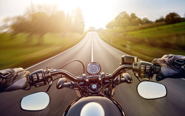 pov shot of young man riding on a motorcycle. hands of motorcyclist on a street - montare foto e immagini stock
