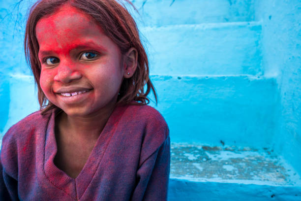 Shot on a blue background, portrait of a 7 year old Indian girl during the Holi Festival in a remote village called Sabalpura. stock photo