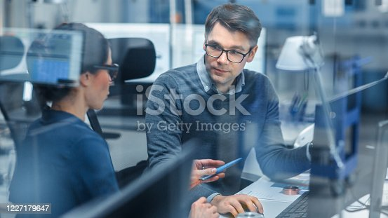 921019684 istock photo Shot Through Glass in Modern Factory: Female Project Supervisor Talks to a Male Industrial Engineer who Works on Personal Computer. Modern High-Tech Industrial Factory Office. 1227179647