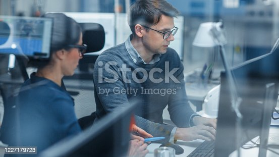 921019684 istock photo Shot Through Glass in Modern Factory: Female Project Supervisor Talks to a Male Industrial Engineer who Works on Personal Computer. Modern High-Tech Industrial Factory Office. 1227179723