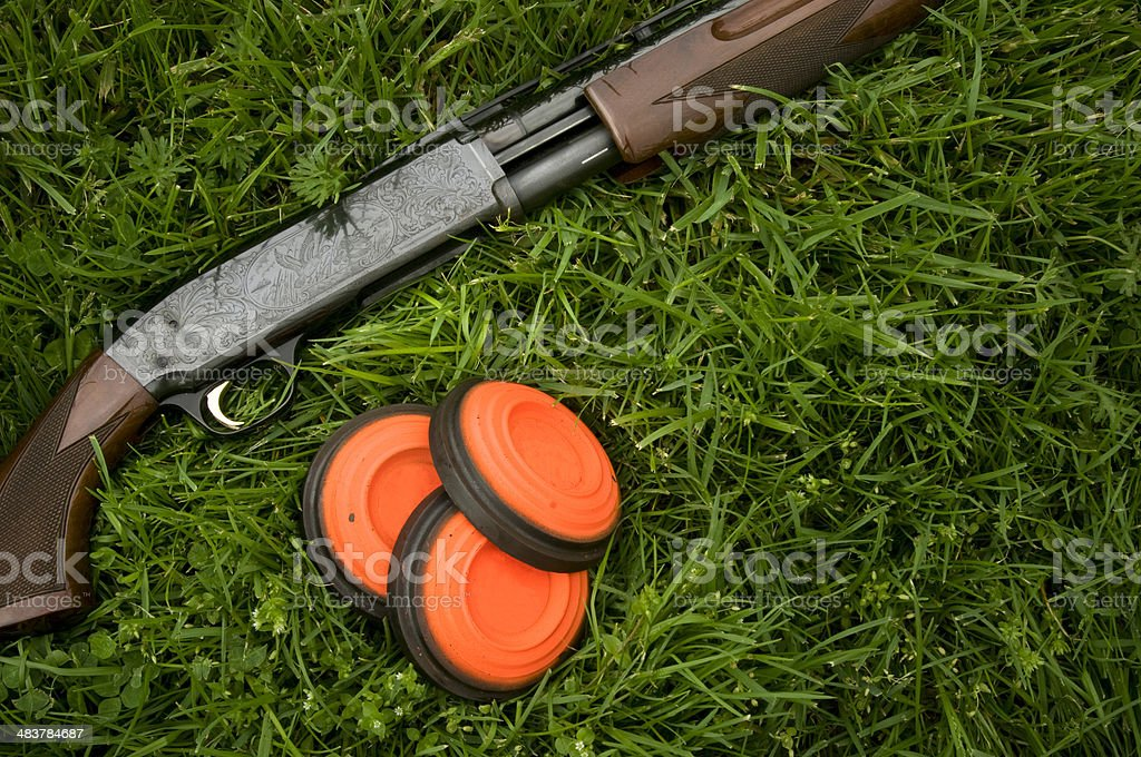 Shotgun and clay pigeons laying in grass stock photo
