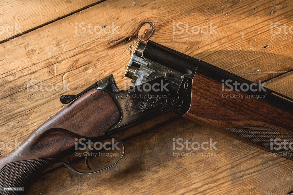 Shotgun charged with bullets and spare bullets on wooden floor, stock photo