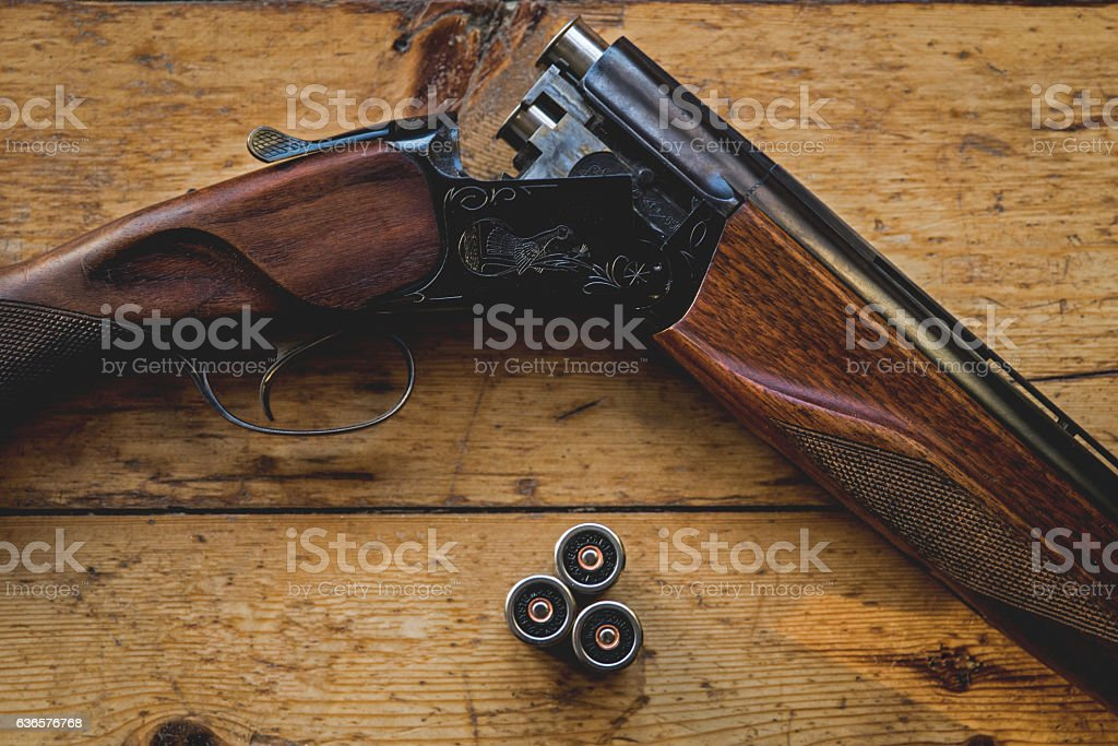 Shotgun charged with bullets and spare bullets on wooden floor, hunting. stock photo