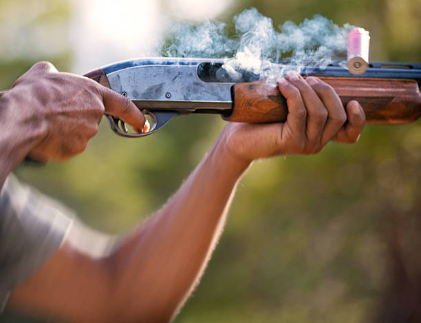 Shotgun fired and shell expelled Close up of shotgun fired and shell ejected from chamber shooting a weapon stock pictures, royalty-free photos & images