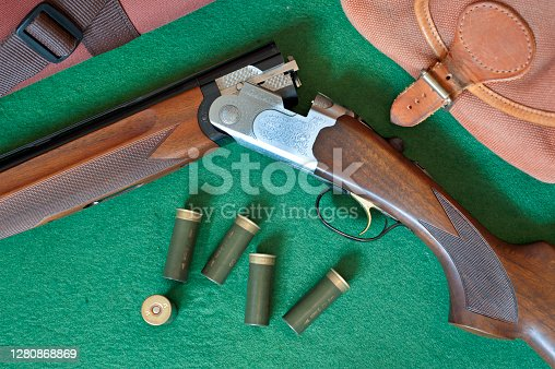 Double barreled shotgun still-life arrangement on green beize background with twelve bore cartridges, wooden carved stock, barrel, leather cartridge case, container and ornate broken gun illustrating the country outdoors sport of either clay shooting or rough shooting