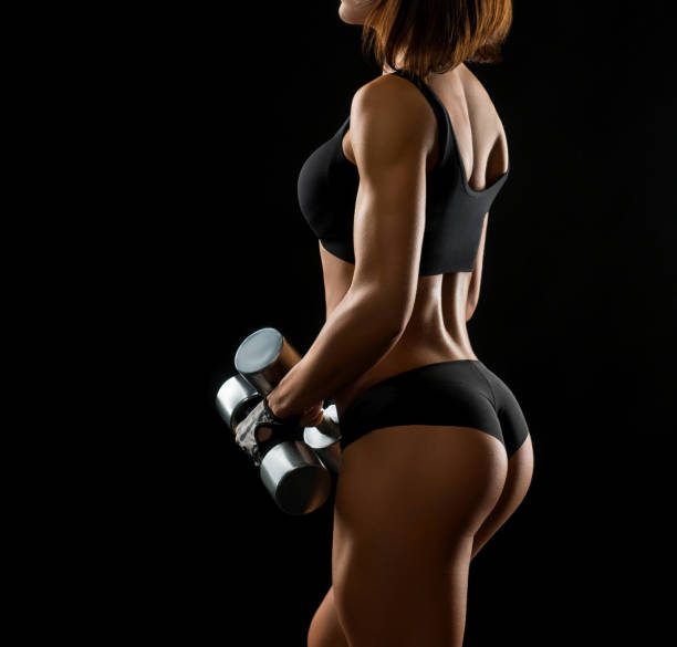 Shots of a fit female with dumbbells Body to be proud of. Closeup shot of a sportswoman in exercise clothing holding weights showing off her stunning body with perfect buttocks on black background hot sexy butts stock pictures, royalty-free photos & images
