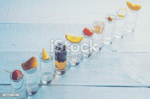 Shots of alcohol on turquoise wooden surface. Inside the ice cubes. On each shot, on top of that lies - radish, lemon, cheese, olive, tomato, Apple and so on.