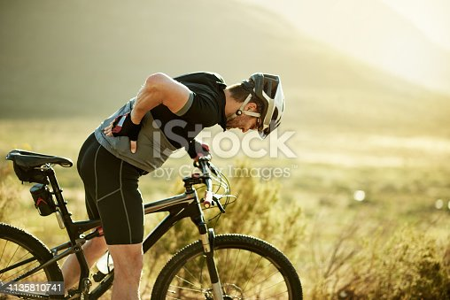 Shot of a mature man experiencing back pain while out for a ride on his mountain bike