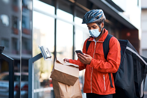 Shot of a masked man using his cellphone while doing a food delivery