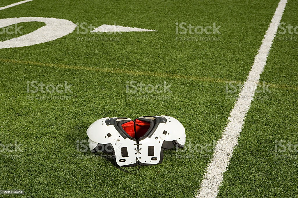 Shoulder pads on football field stock photo