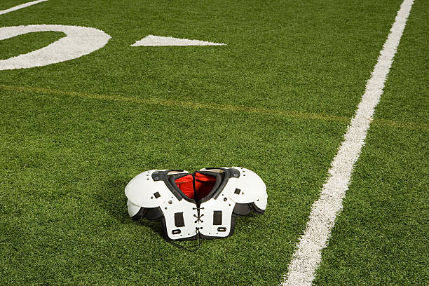 Shoulder pads on football field Shoulder pads on football field safety american football player stock pictures, royalty-free photos & images